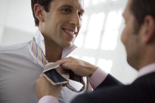man helping his friend to tie his tie Keine Weitergabe an Drittverwerter., Royalty free: Bei werblicher Verwendung Preis auf Anfrage